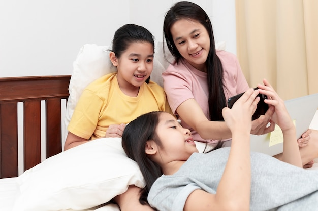 Familia asiática disfrutar y relajarse en la cama en el dormitorio madre e hijas disfrutan usando la computadora portátil