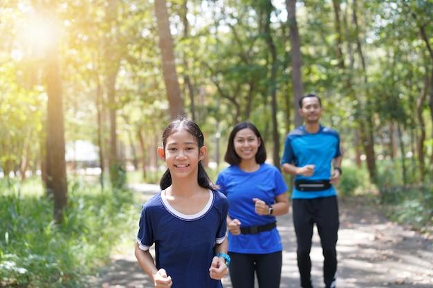 Familia asiática haciendo ejercicio y trotando juntos en el parque