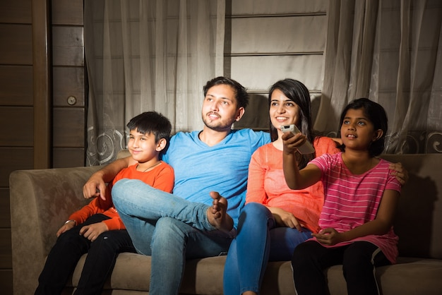 Familia asiática india de cuatro viendo la televisión o la televisión mientras está sentado en el sofá o el sofá