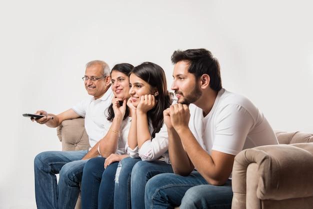 Familia asiática india de varias generaciones viendo la televisión en casa mientras está sentado en un sofá o sofá, vista lateral, enfoque selectivo