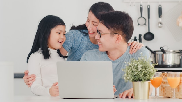 La familia asiática joven disfruta usando la computadora portátil juntos en casa. estilo de vida joven esposo, esposa e hija feliz abrazo y jugar después de desayunar en la cocina moderna en casa por la mañana.