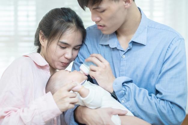 Familia asiática joven padre y madre alimentación leche bebé en casa. retrato de pareja joven asiática padre madre sosteniendo el recién nacido concepto de día de la madre de la guardería infantil