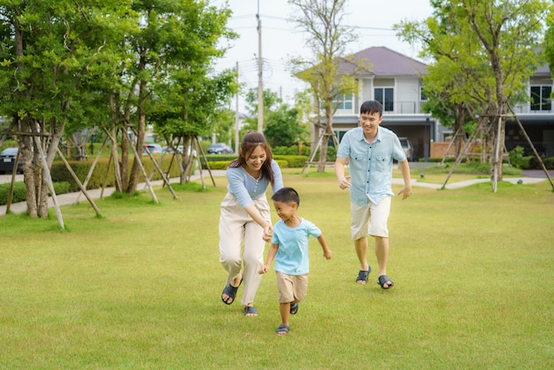 Familia asiática jugando a atrapar en el patio o en el parque público en el vecindario para la salud y el bienestar diario, tanto física como mental, familia feliz.