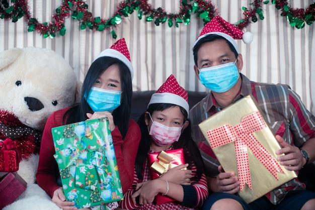Familia asiática, en, navidad, interior., feliz, madre, padre e hija, llevando, mascarilla, y, tenencia, un, caja de regalo, con, sonrisa