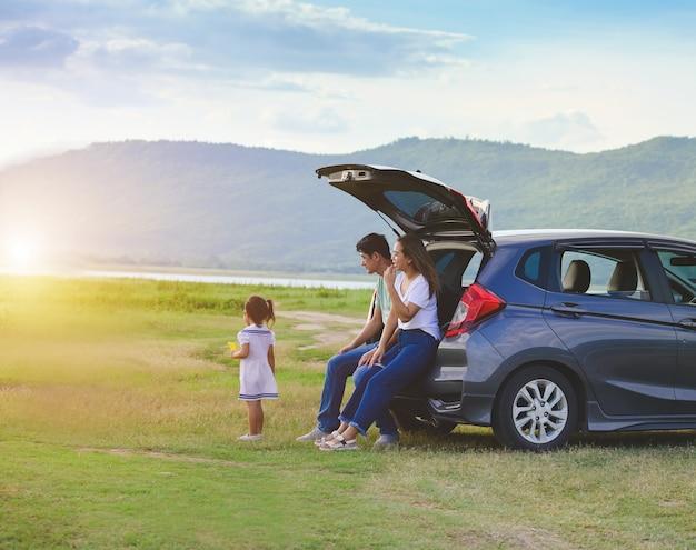 Familia asiática niña feliz con familia sentada en el coche. concepto de seguro de coche
