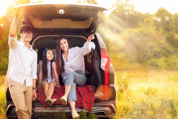 Familia asiática padre, madre e hija juegan juntos en el coche