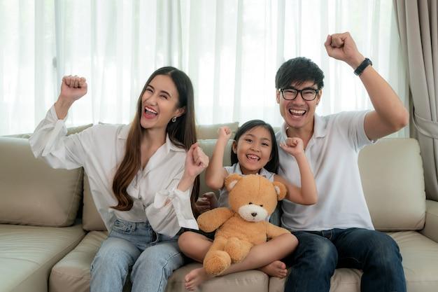 Familia asiática con padre, madre e hija sentados y viendo televisión y sonríen