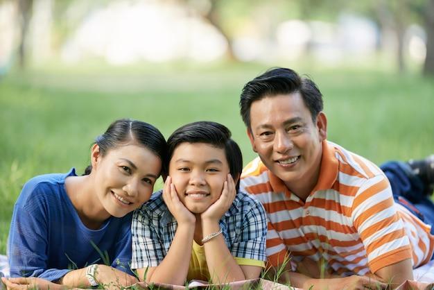 Familia asiática en el parque público verde