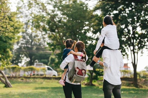 La familia asiática está saliendo de la casa, los padres llevan y los niños dan la espalda.