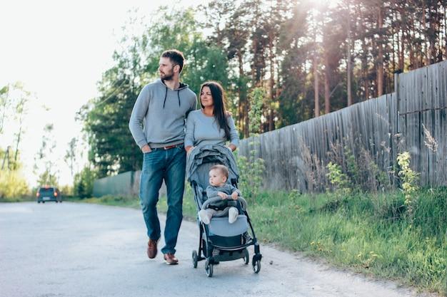 Familia auténtica con lindo bebé bo sentado en la carriola caminando