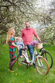 Familia en una bicicleta en el jardín de primavera