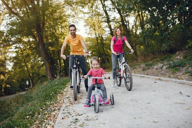 Familia con una bicicleta en un parque de verano