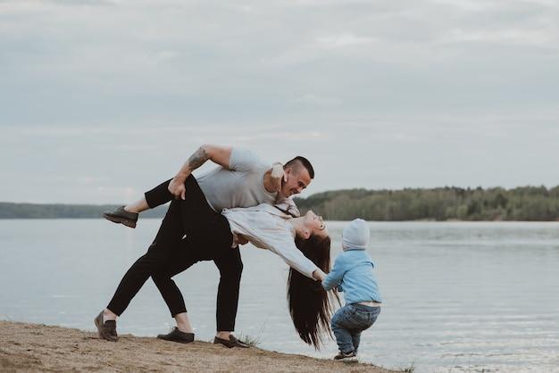 Familia blanca joven con su hijo en la playa en la arena en el verano junto al río