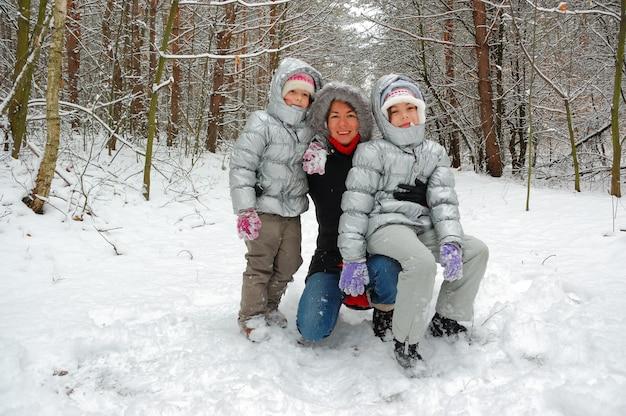 Familia en bosque de invierno, madre feliz y niños divirtiéndose al aire libre