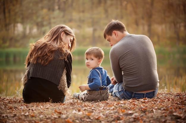 Familia en el bosque de otoño, vista desde atrás