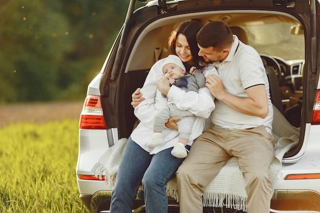 Familia en un bosque de verano junto al tronco abierto