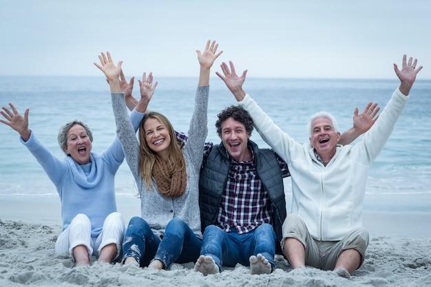 Familia con los brazos levantados sentado a la orilla del mar