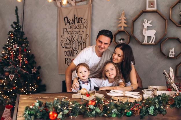 Familia cacasiana feliz en la acogedora casa de vacaciones decorada con luces de navidad. alegres niños y padres celebran fiestas tradicionales