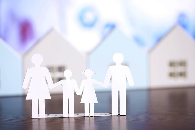 Familia de cadenas de papel recortadas con protección de manos ahuecadas, concepto de seguridad y cuidado. manos con silueta de papel cortado en la mesa. concepto de cuidado familiar