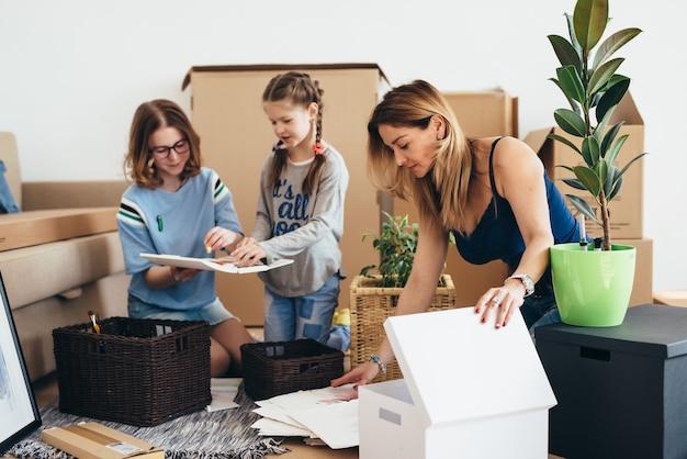 Familia con cajas de cartón en casa nueva en el día de la mudanza.