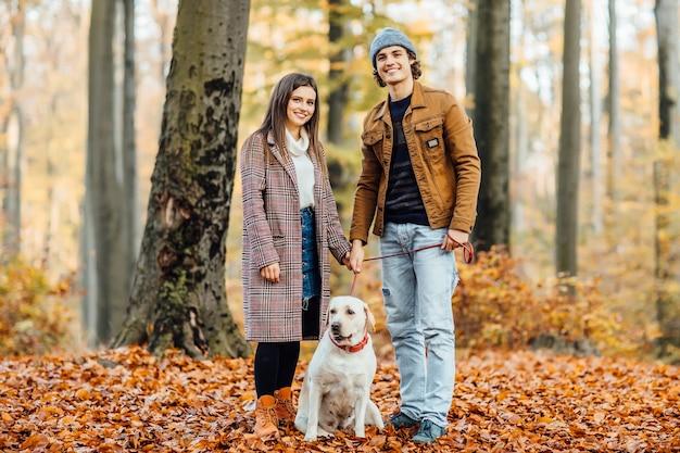 Familia caminando con labrador dorado en collar rojo en el parque otoño
