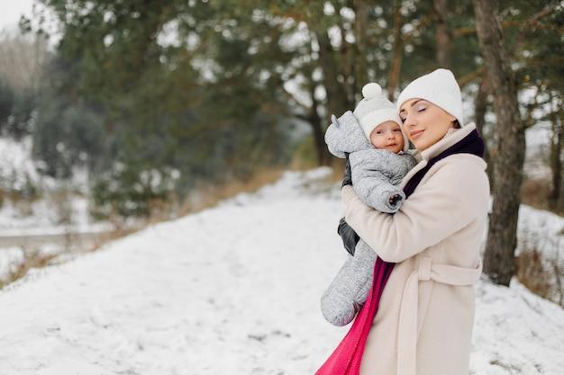 Familia caminando en la nieve divirtiéndose en winter park en un día brillante abrazándose y sonriendo