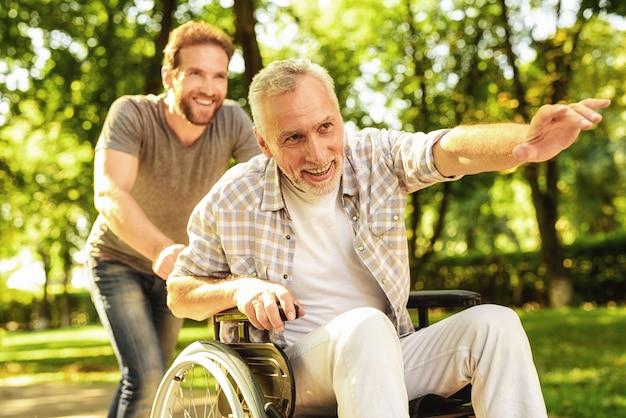 Familia caminando en el parque old man sentarse en silla de ruedas