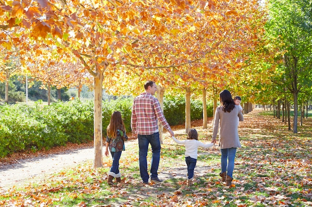Familia caminando en un parque de otoño