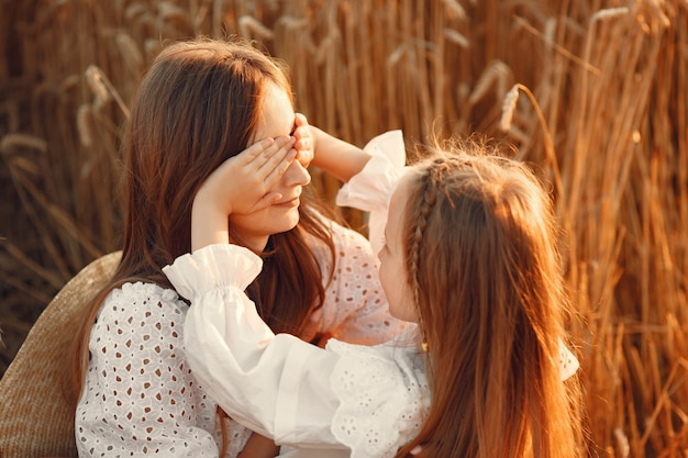 Familia en un campo de trigo. mujer con un vestido blanco. chica con sombrero de paja.