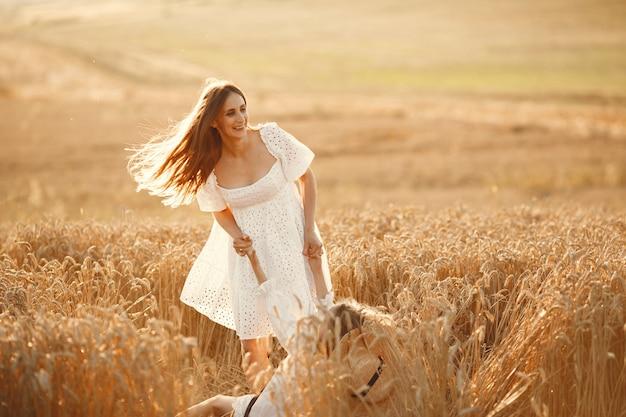 Familia en un campo de trigo. mujer con un vestido blanco.
