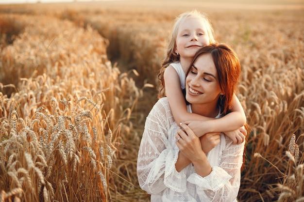 Familia en un campo de verano. foto sensual. pequeña niña bonita. mujer con un vestido blanco.
