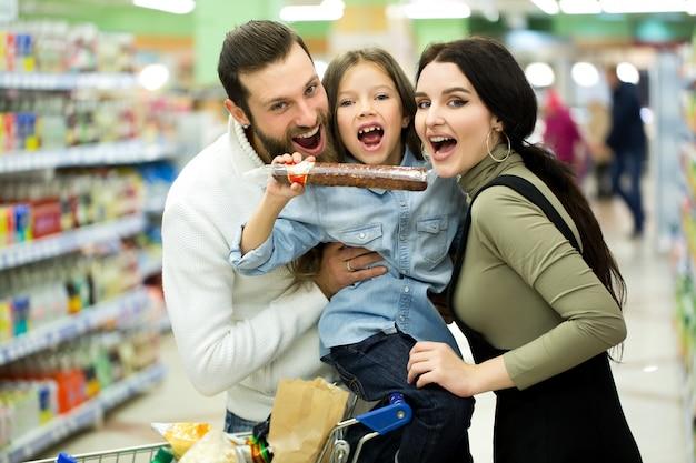 Familia con carrito de compras con comida visitando supermercado
