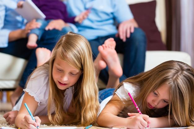 Familia en casa, los niños coloreando en el piso