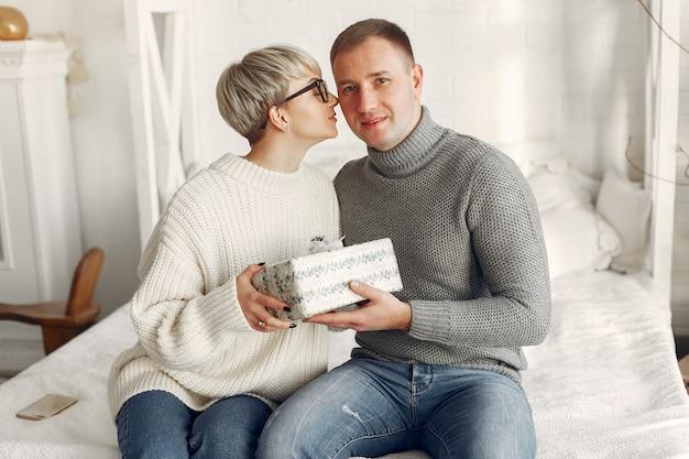Familia en casa. pareja cerca de adornos navideños. mujer con un suéter gris.
