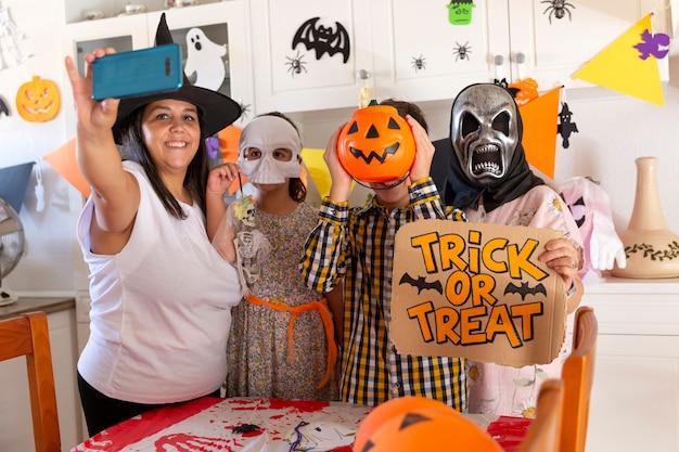 Familia en casa tomando una foto con el teléfono móvil mientras celebra la fiesta de halloween.