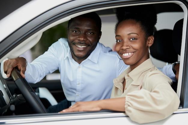 Familia casada negra examinando el coche desde el interior