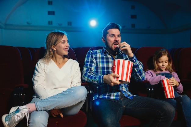 Familia caucásica joven viendo una película en una sala de cine, una casa o un cine. luce expresivo, asombrado y emocionado. sentarse solo y divertirse. relación, amor, familia, infancia, fin de semana.