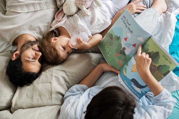 Familia caucásica leyendo cuentos de hadas a su hija con felicidad.