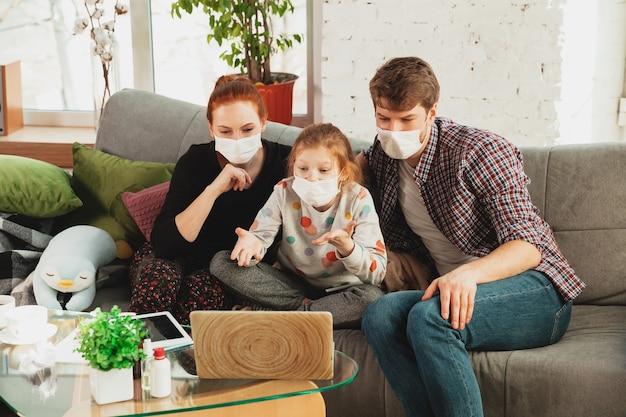 Familia caucásica en máscaras protectoras y guantes aislados en casa