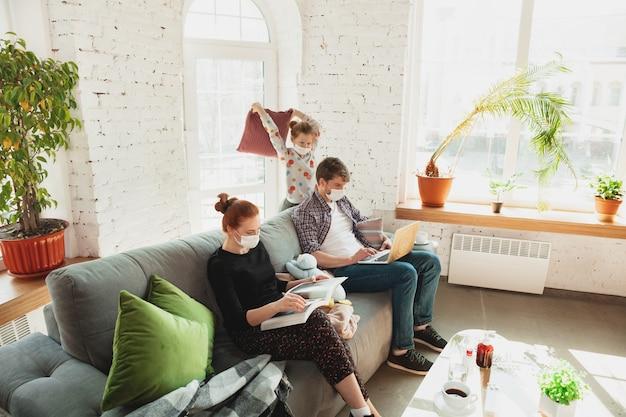 Familia caucásica en mascarillas y guantes aislados en casa con coronavirus