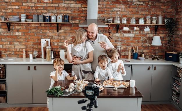Familia caucásica transmitiendo su actividad de ocio y estilo de vida doméstico en la televisión. programa de televisión moderno de tres niños pequeños y sus padres.