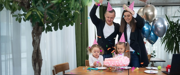 La familia celebra el cumpleaños en un café, los padres tiran la serpentina. pastel y bolas.