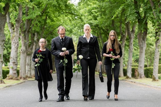 Familia en el cementerio caminando por el callejón en el cementerio con rosas