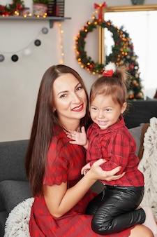 Familia cerca del árbol de navidad. feliz madre de familia y el bebé cerca del árbol de navidad en vacaciones. feliz navidad y felices fiestas! familia amorosa con regalos en la habitación.