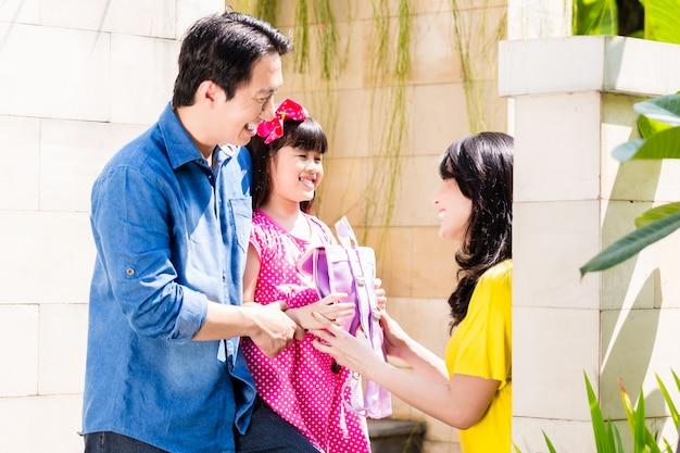 Familia china enviando niña a la escuela