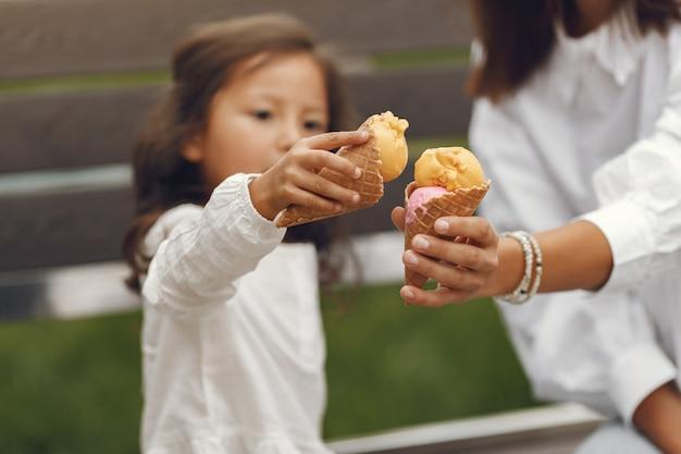 Familia en una ciudad. niña come helado. madre con hija sentada en un banco.