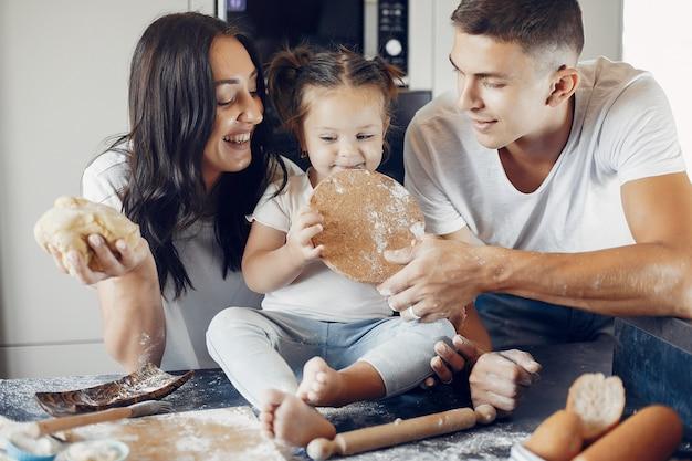 Familia cocina la masa para galletas en la cocina