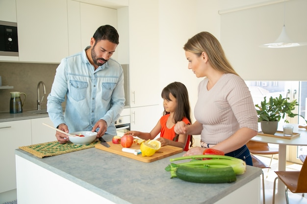 Familia cocinando la cena en casa durante la pandemia. pareja joven y niño cortando verduras para ensalada en la mesa de la cocina. nutrición saludable o concepto de comer en casa
