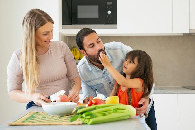 Familia cocinando y comiendo en casa durante una pandemia. niña dando una rebanada de verduras a papá para que le dé sabor mientras mamá corta verduras y frutas frescas. concepto de estilo de vida o cocina familiar