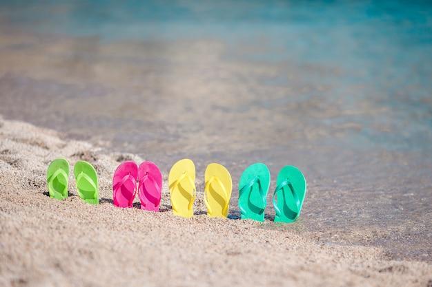 Familia coloridas chanclas en la playa frente al mar